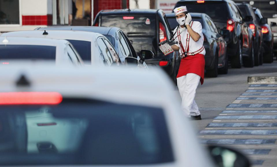 An In-N-Out associate in Los Angeles wears a mask while taking orders from cars in the drive-through lane at a restaurant in July.