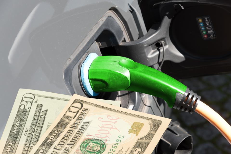 An electric car and dollar banknotes