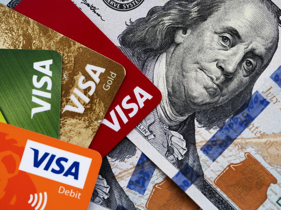 In this photo illustration, Visa credit cards and a portrait...