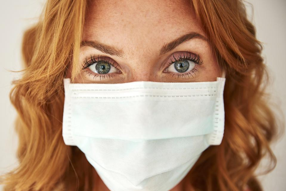 Portrait of red-haired woman wearing a face mask at home