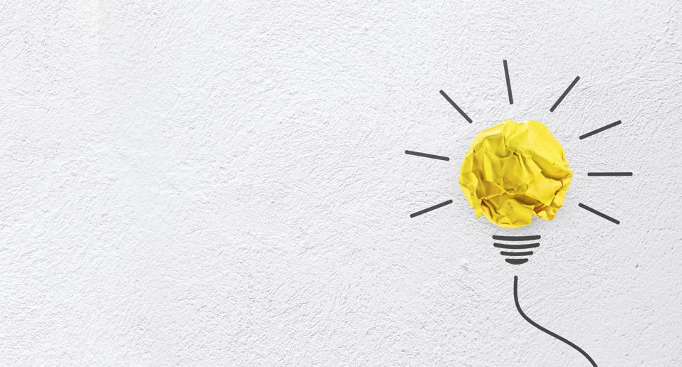 Ideas with yellow paper crumpled ball on wall( lightbulb ).