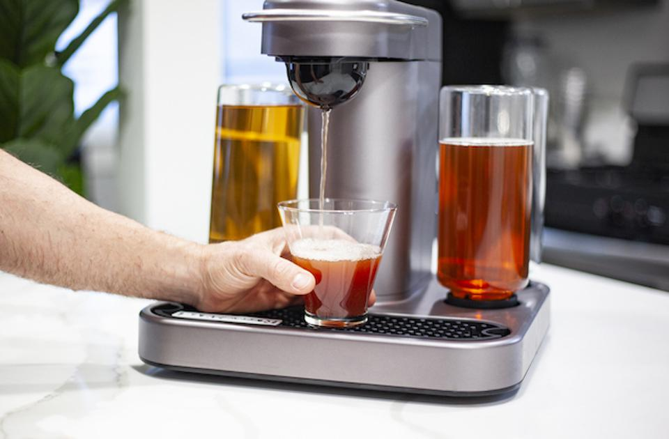 A machine pouring a cocktail into a glass.