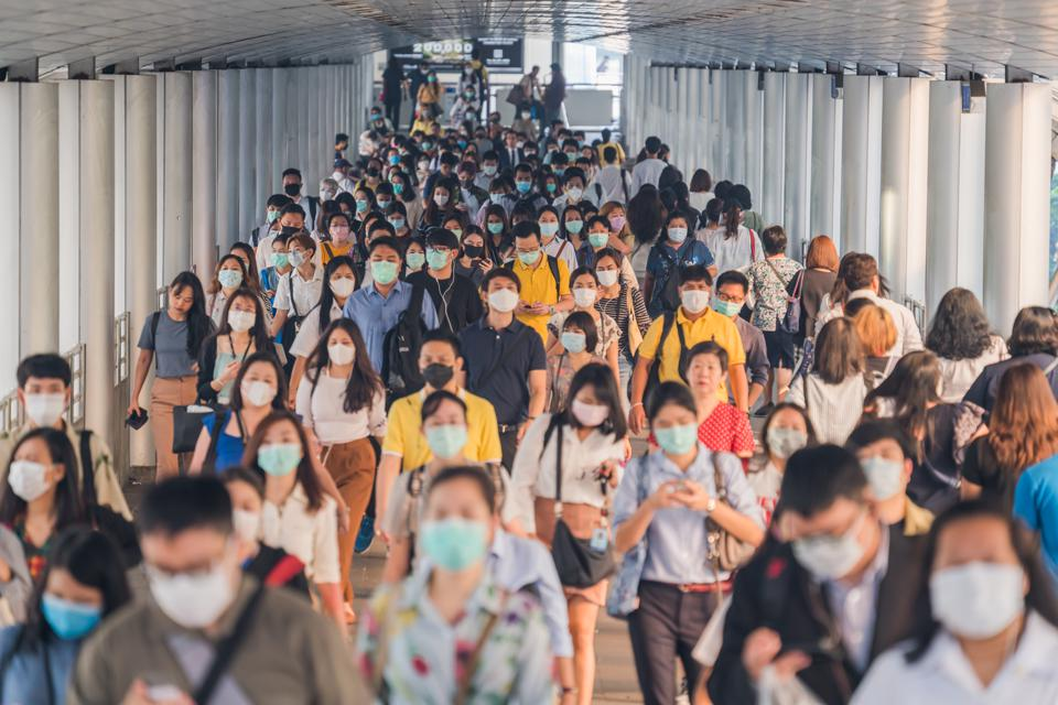 Crowds of people wearing face protection at morning rush hour