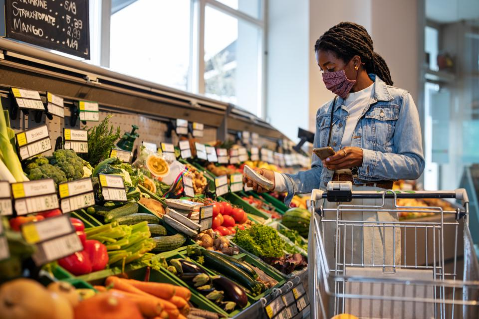 Female customer with face mask buying fresh fruits from produce aisle in supermarket.