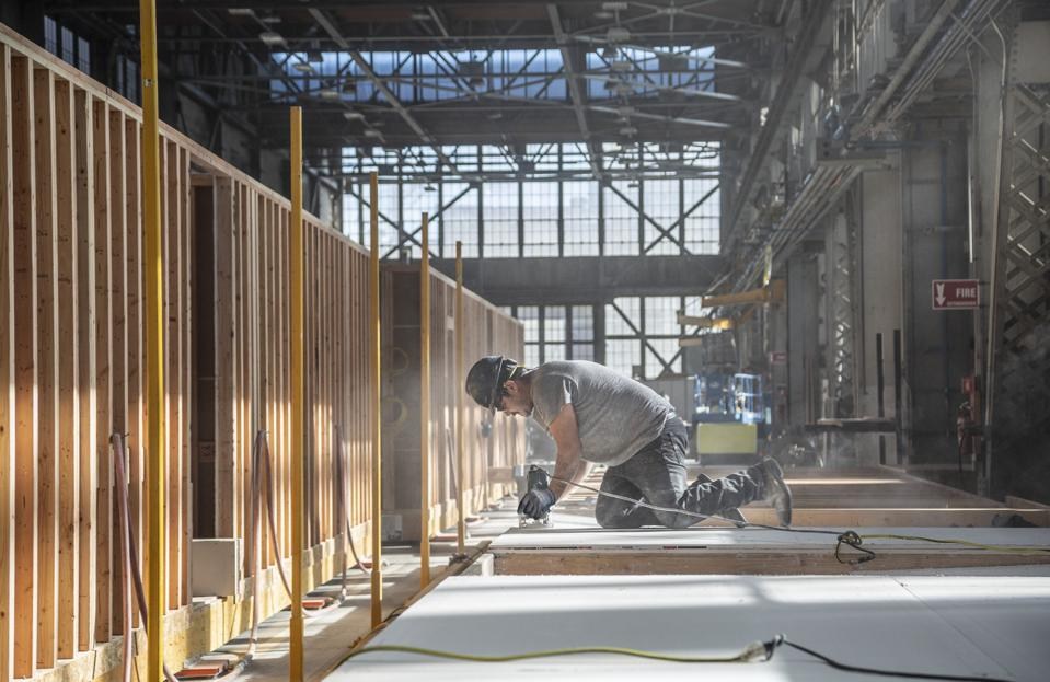 A worker cuts wall utility openings at Mare Island