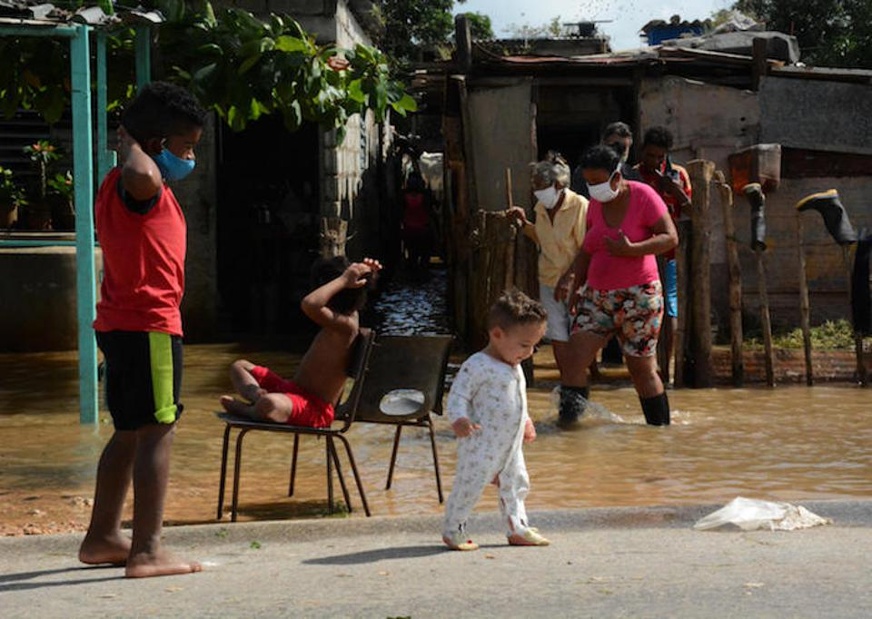 Climate change is making hurricanes and other seasonal weather emergencies more dangerous. Above, children in the province of Ciego de Avila, Cuba play on a patch of dry ground surrounded by floodwaters after Hurricane Eta battered the region.