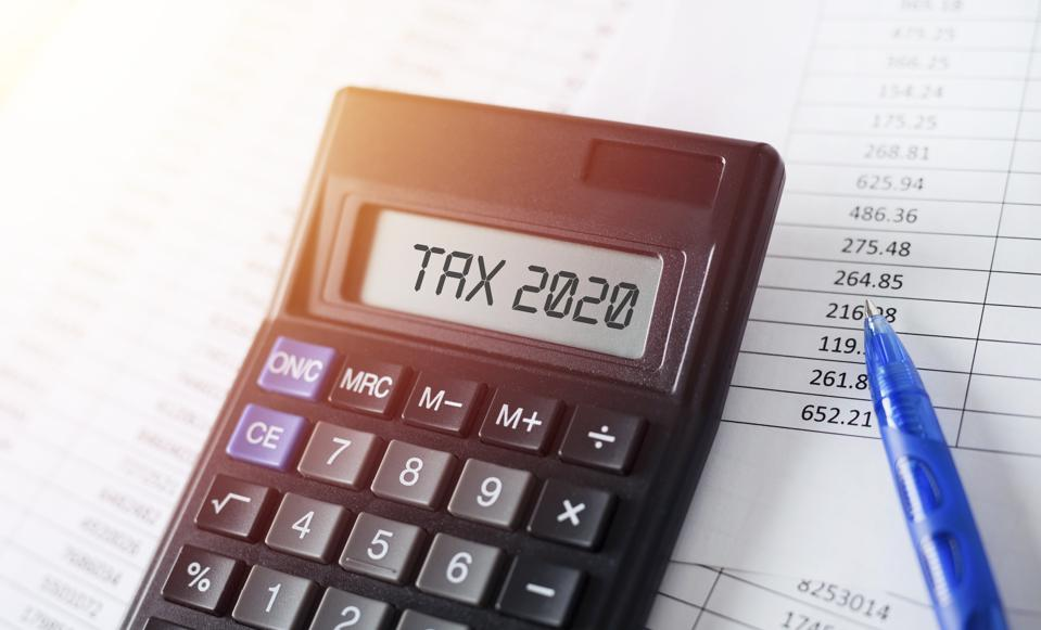Word Tax 2020 on calculator. Business and tax concept.
