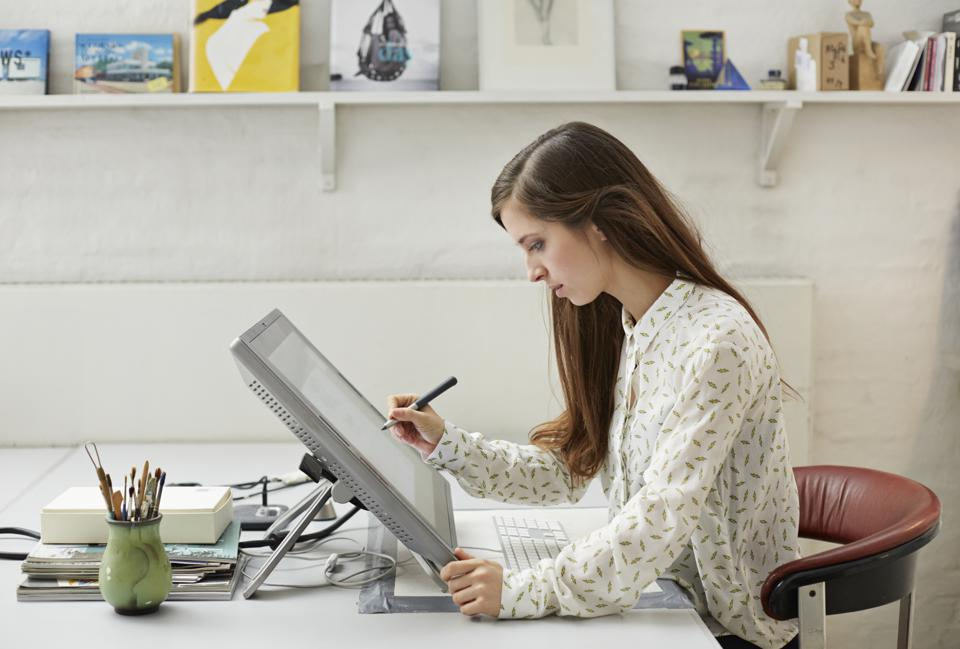 Young graphic designer working with pen on screen
