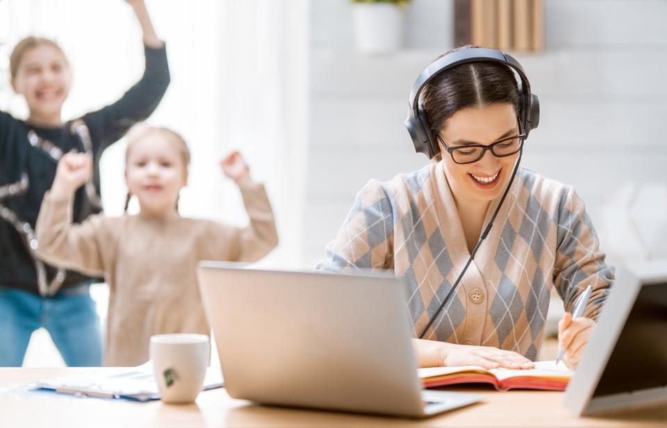 Young smiling mother in home office works in headphones while her kids jump & play nearby.