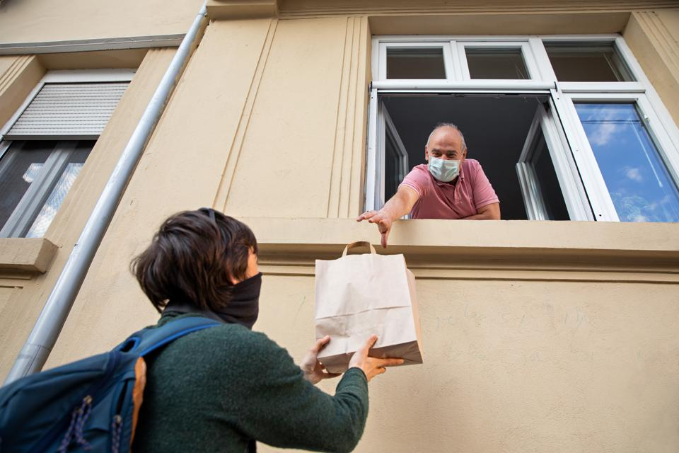 Delivery person hands bag to customer. Both wear masks. Both are smart.