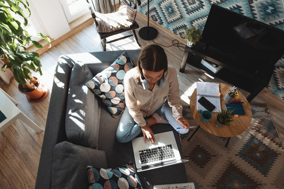 Woman working from home surrounded by throw pillows that probably cost way too much.