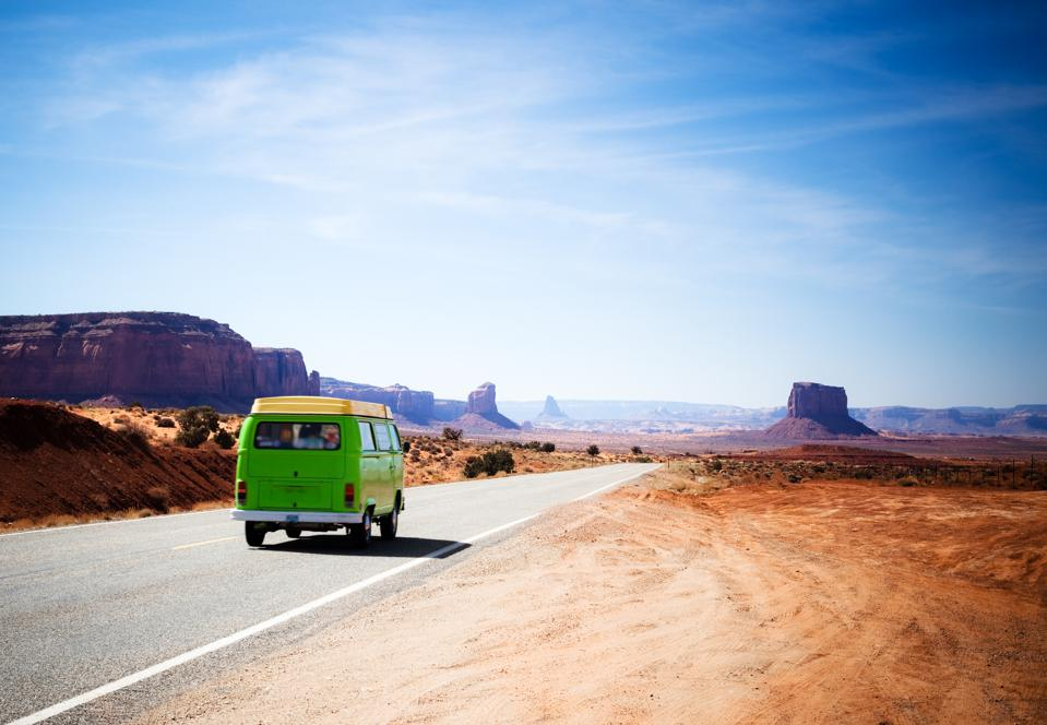 Travelling in the Monument Valley With a Green Old Van