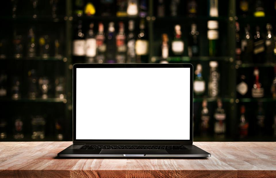 Modern computer,laptop on counter bar with blur wine bottle
