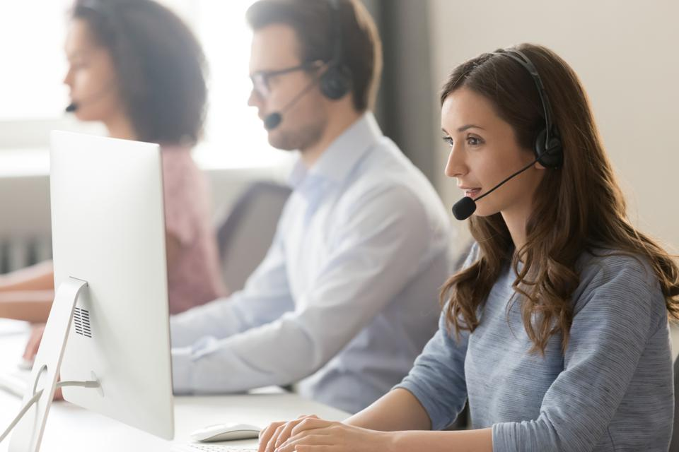 Female agent in headset consult client online using pc