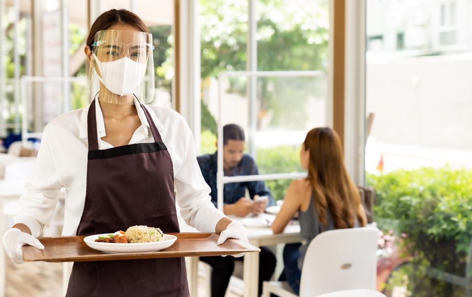 Camarera asiática sirviendo comida nueva normal.