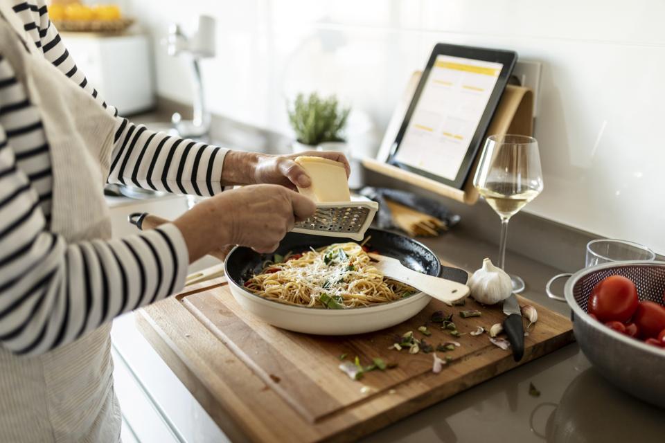 Primer plano de mujer con tableta cocina plato de pasta en la cocina de casa