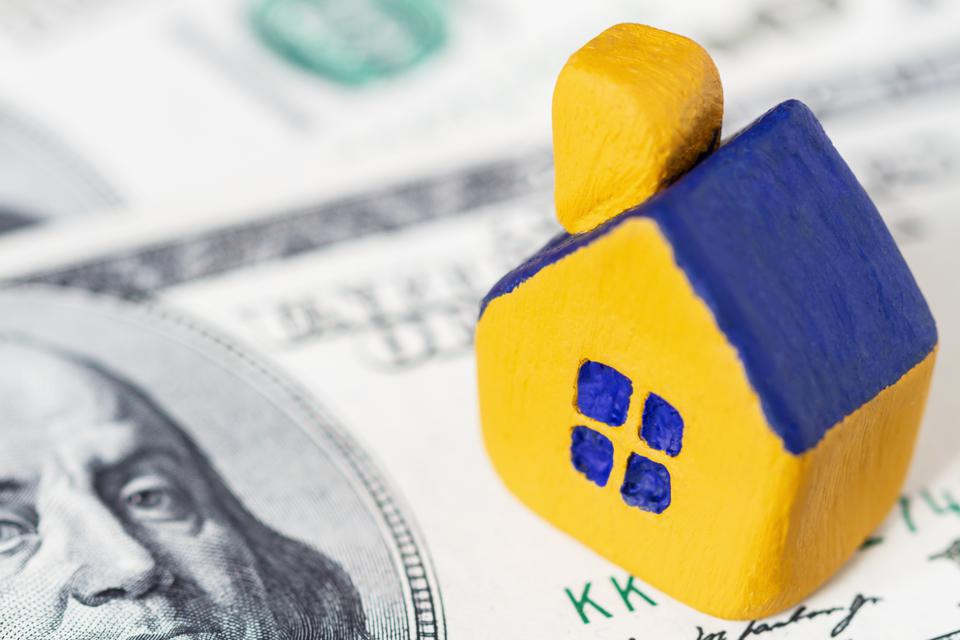 Miniature yellow toy house with a blue roof on 100 (one hundred) dollars bill. Selective focus.