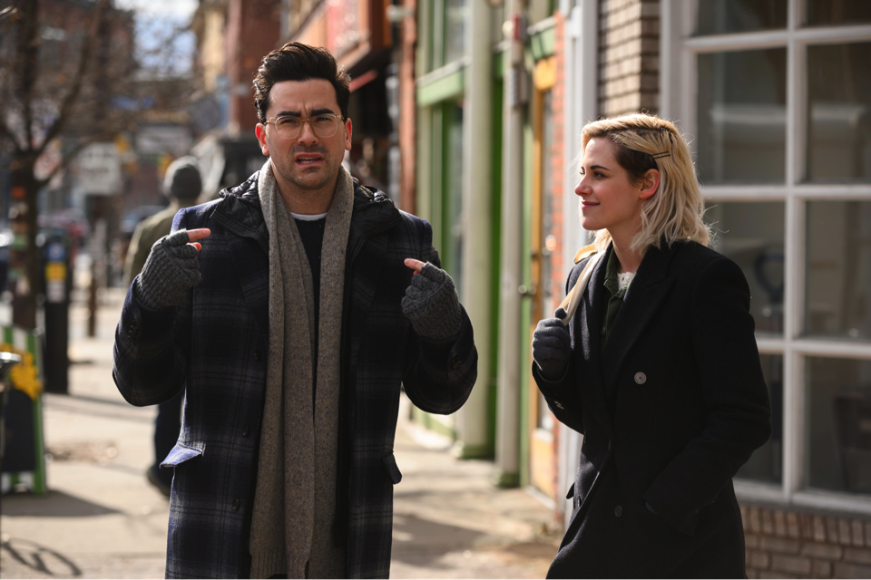 A man and a women walk down a street are engaged in conversation.