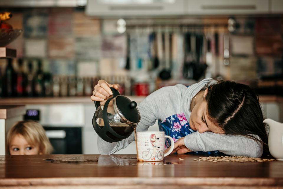 Tired mother, trying to pour coffee in the morning. Woman lying on kitchen table after sleepless night