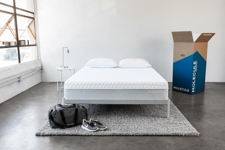 Molecule mattress set up with gym bag and sneakers at the foot of the bed