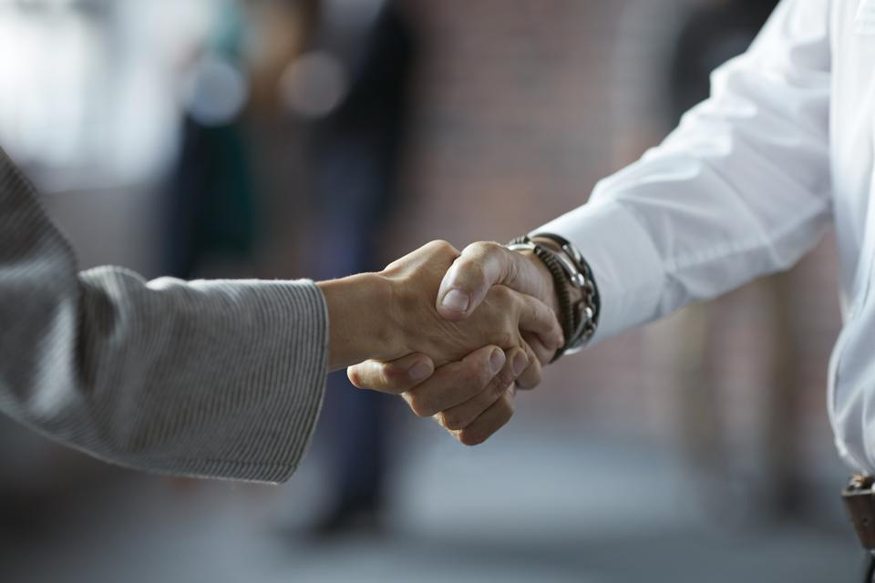 Businesspeople making handshake at conference
