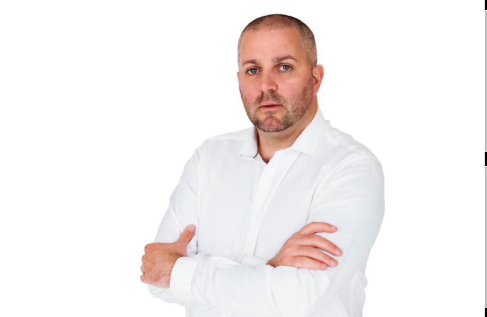 Man, grey beard wearing a white button up dress shirt
