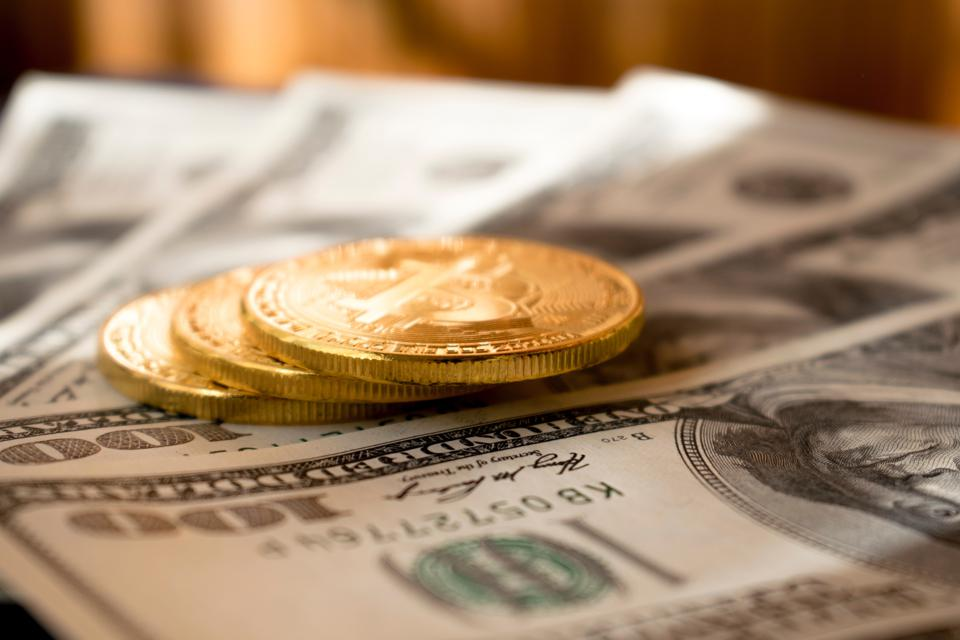 100 dollar bills with bitcoins sitting on top.