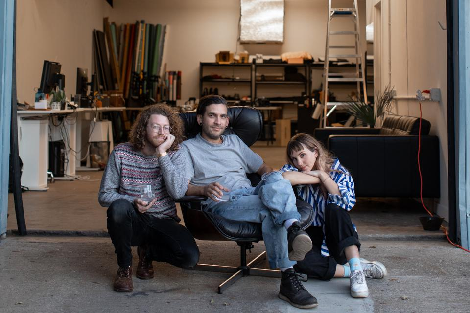 Marshall Tidrick sits with studio co-founders in front of their Austin studio.
