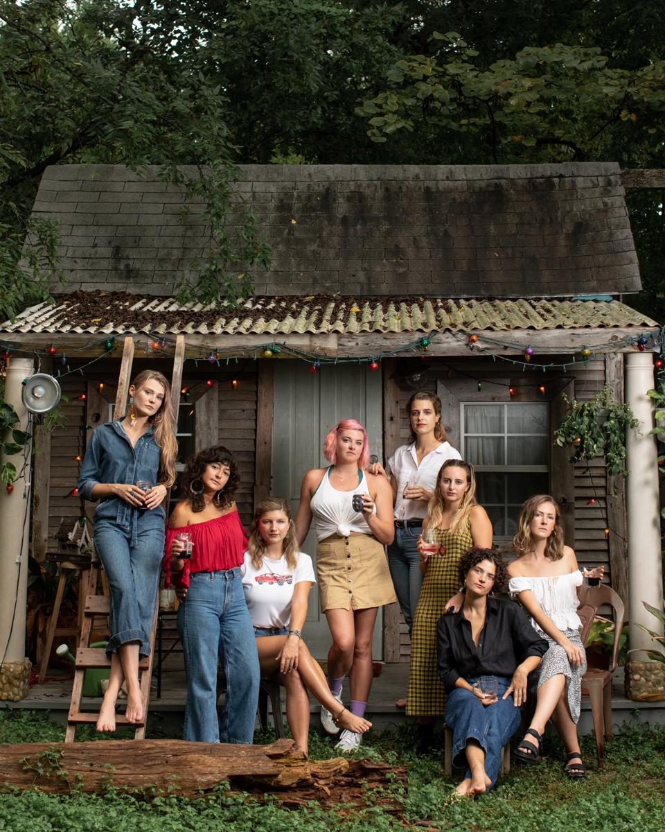 Ally, Lesly, Lily, Wesley, Bradley, Tatiana, Caitlin, and Mary Elizabeth on the front porch of the tiny house in one of their backyards.