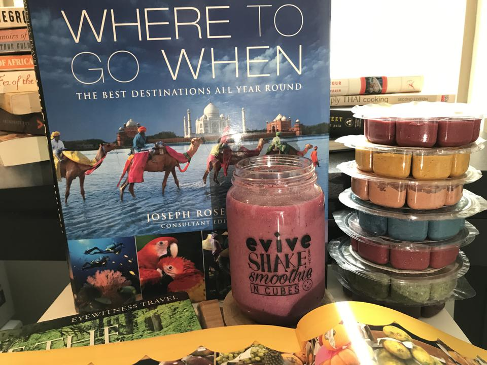Several travel books next to a glass of a pink smoothie and a stack of Evive's freezer smoothie cubes