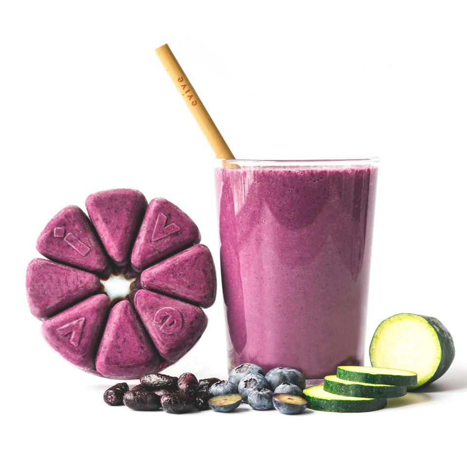 A purple smoothie in a glass with blueberries, haksap berries, and zucchini in front of it. Beside it is a ring of eight triangular packs containing the frozen smoothie mixture.