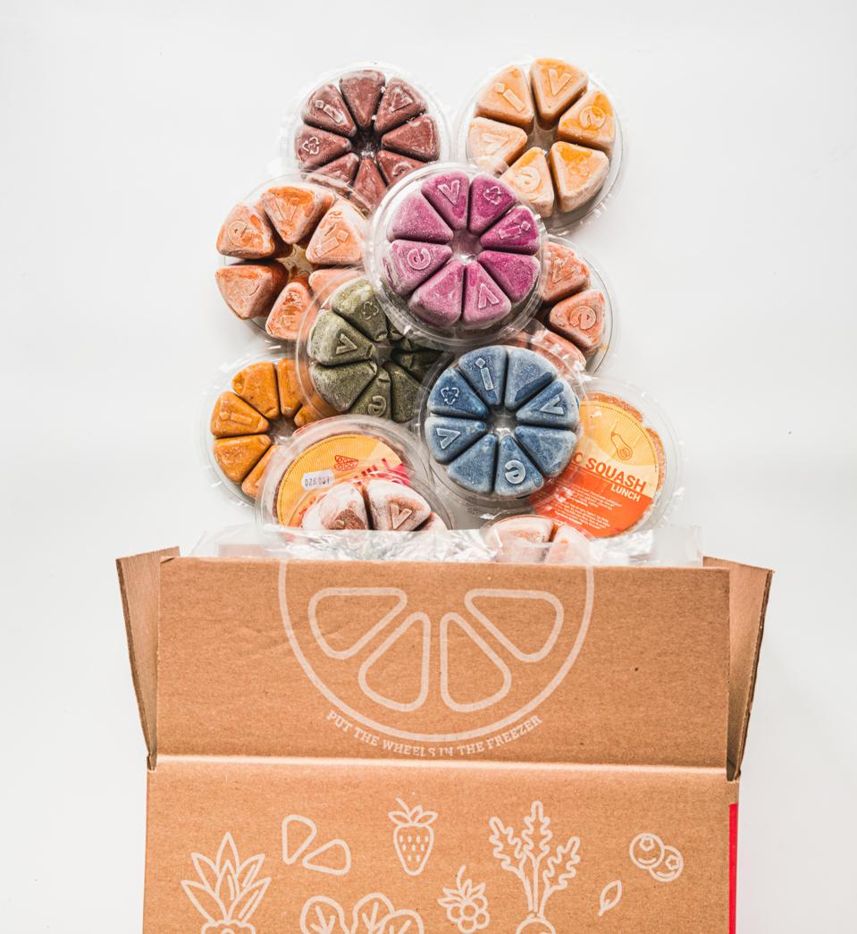 A dozen wheels of frozen smoothie packs spill out of a cardboard box