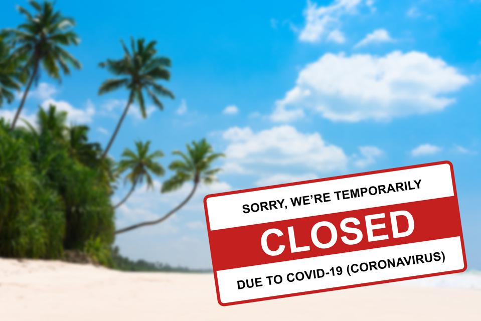 Tropical beach on island resort closed due to Coronavirus Covid-19 sign