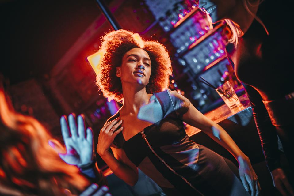 Young multi-ethnic woman dancing in a bar during a night out