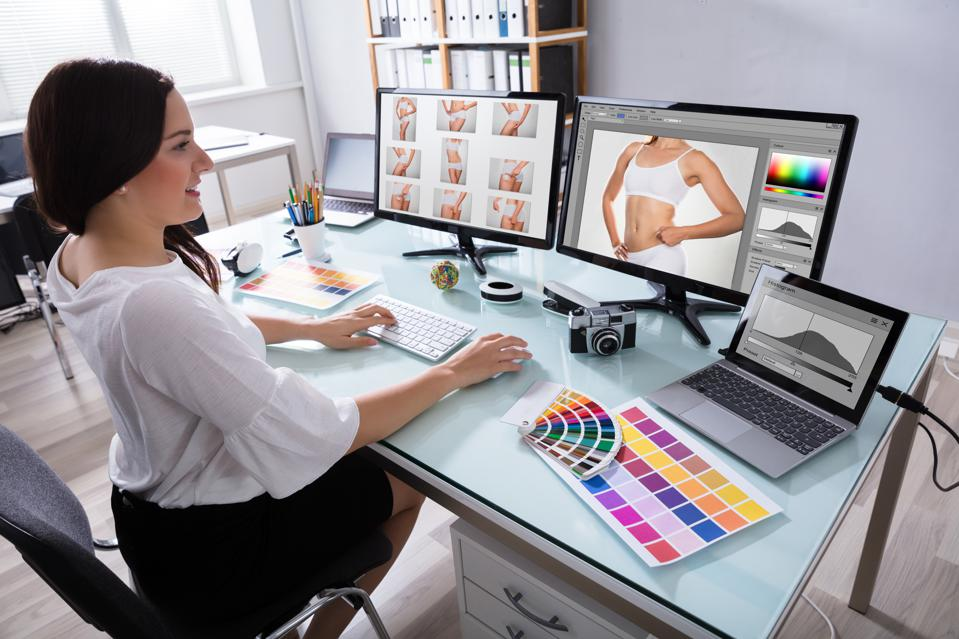 Female Designer Working With Photographs On Multiple Computer