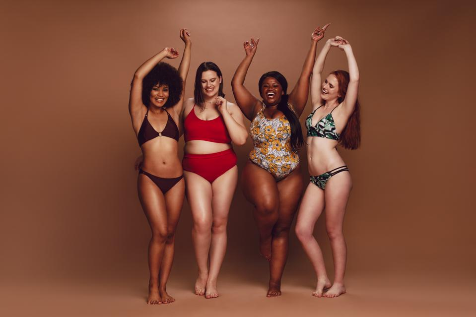 Women of different sizes in bikinis dancing together