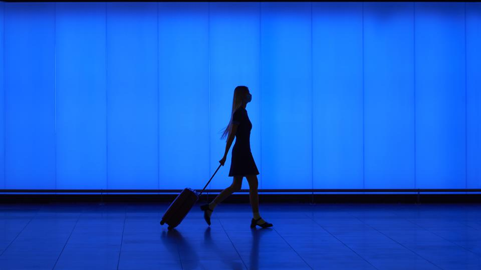Silhouette of walking woman with suitcase
