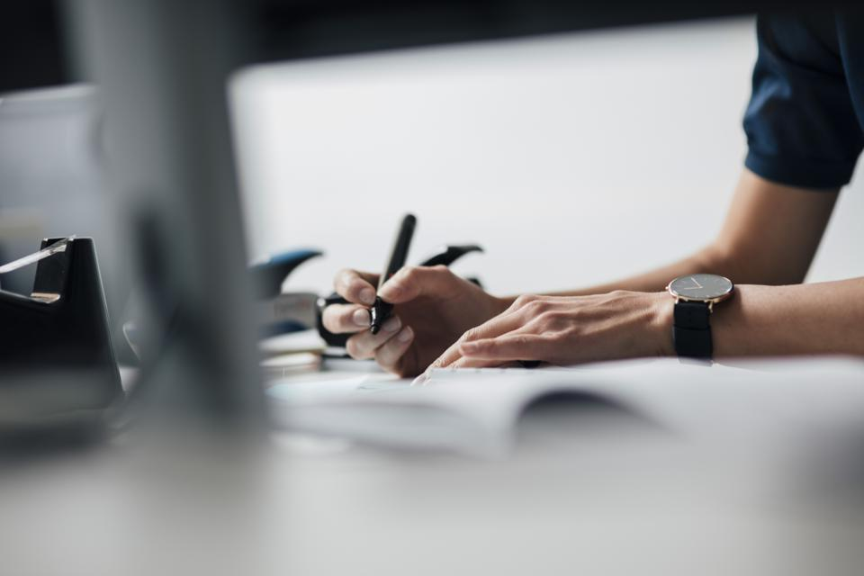 Cropped image of businesswoman writing at desk in office