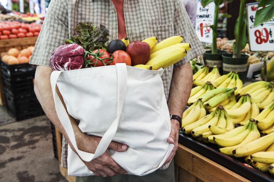 Close up of person at a food and vegetable market, holding shopping bag with fresh produce including bananas, tomatoes and cabbage.
