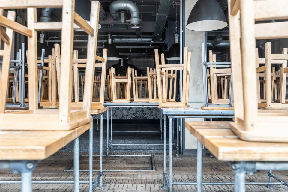 Chairs turned up onto tables in empty restaurant during Corona virus crisis.