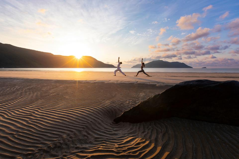 The sun rising over the mountains while two people do yoga stretches on a rippled beach