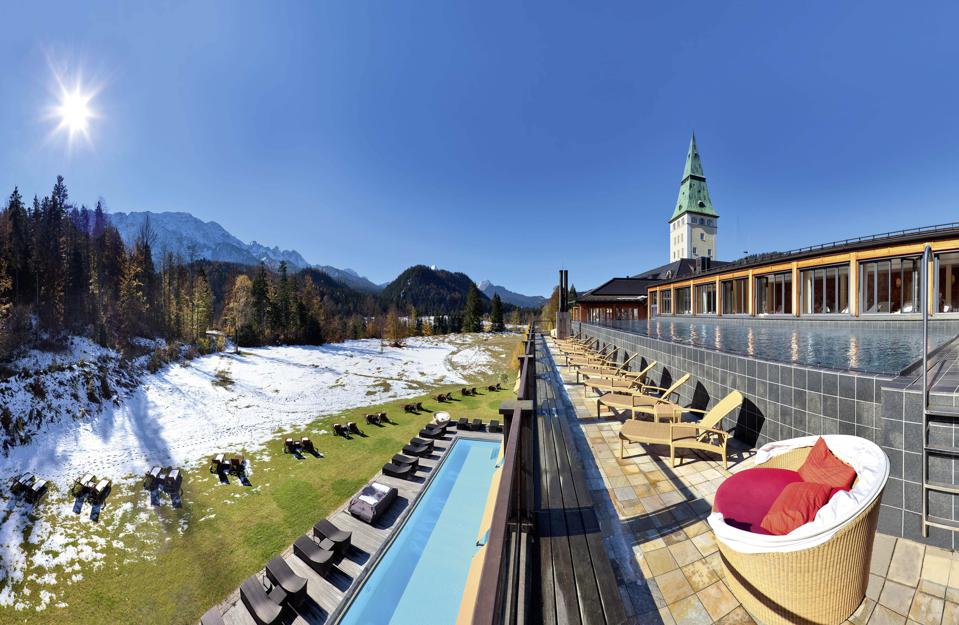 A spa swimming pool and main resort building spire with snow on the grounds and the sun rising over the Alps