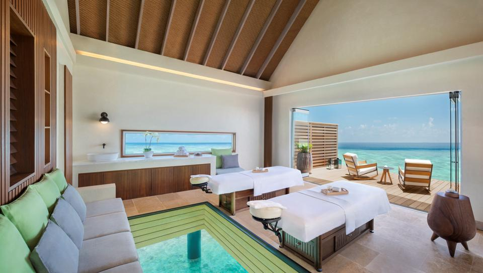 An open spa suite overlooking turquoise water