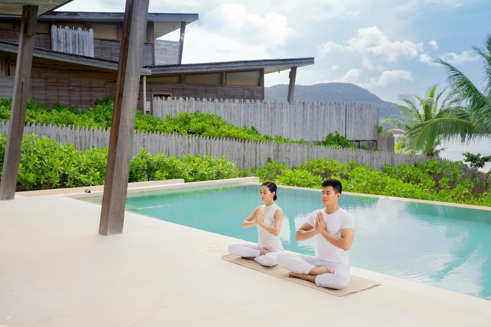 Two people in yoga poses by a swimming pool with the ocean in the background