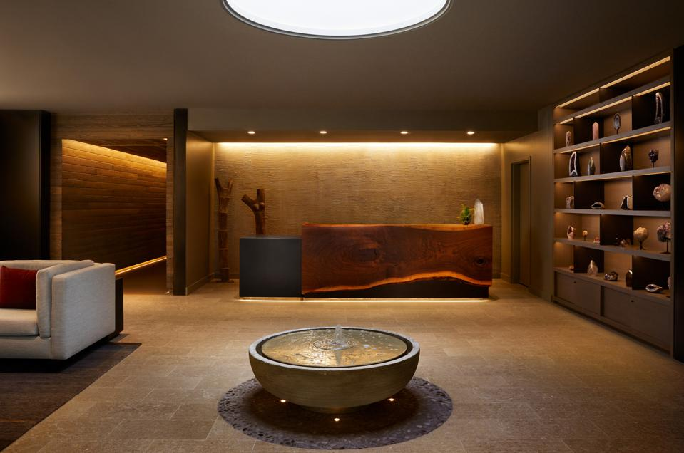 A low lit, bronze colored room with a fountain in the center