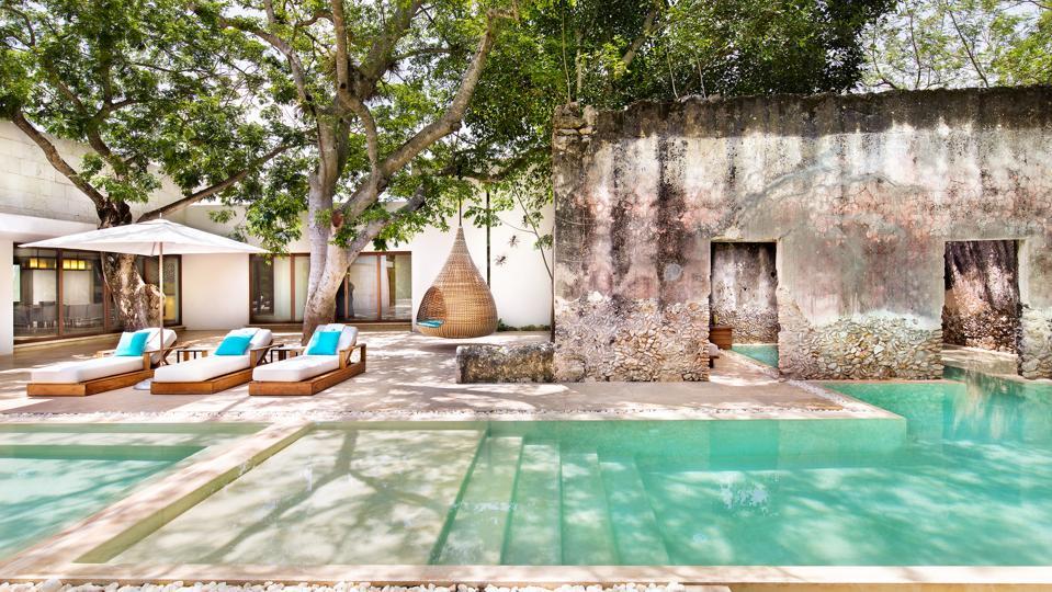A pool set against rustic stone buildings