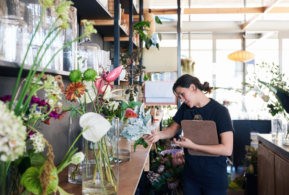 Florist standing in her flower shop talking on the phone