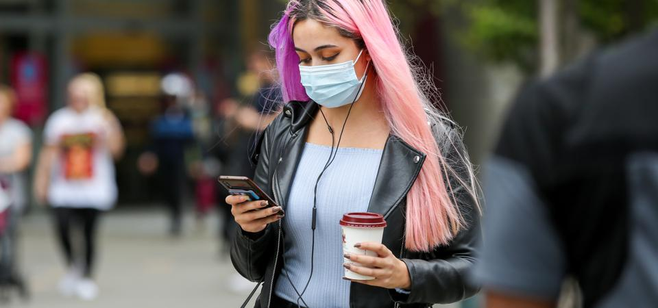 A woman wearing a face mask looks at her mobile phone...