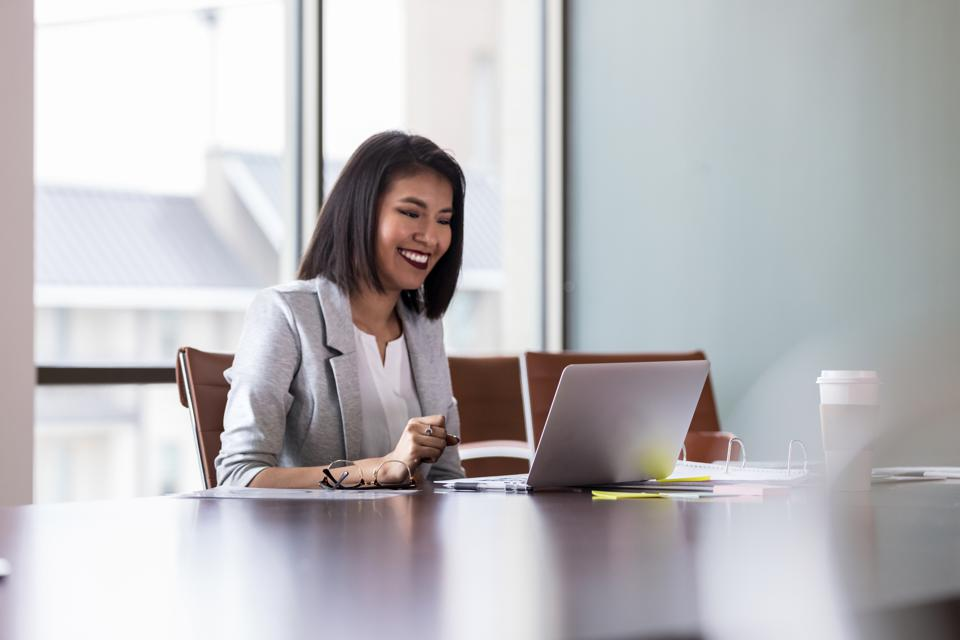 Cheerful young businesswoman video chats with colleague