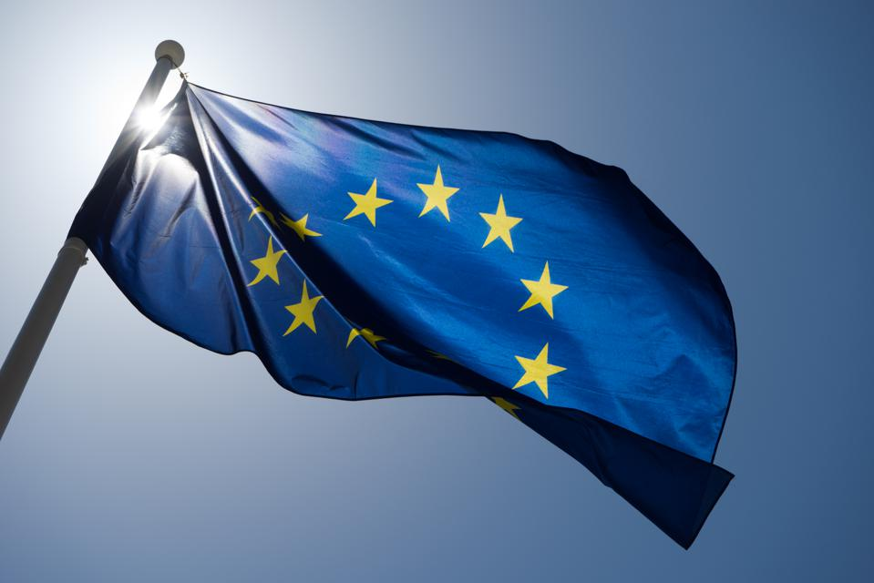 Series of images of the EU flag flying in the wind, backlight and blue sky